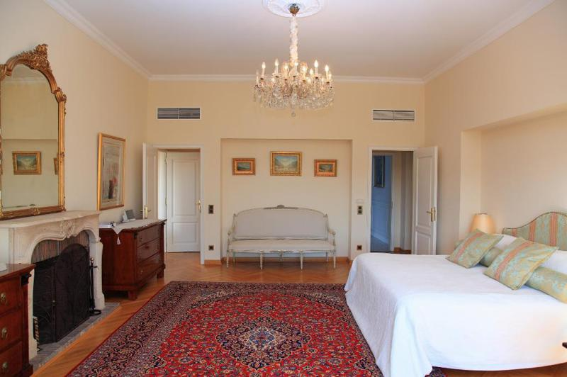 Double bedroom with a colourful rug, a fireplace and a couch in Cannes