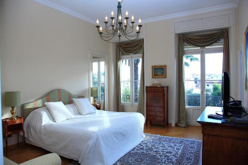 Double bedroom with a white blanket, a flat screen tv and a candle chandelier hanging from the roof in a Cannes rental villa
