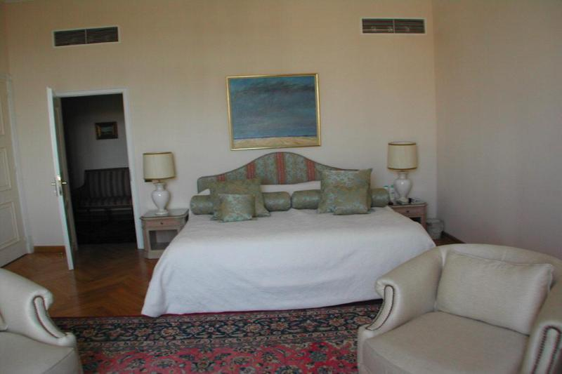 Double bedroom with 2 cream coloured couches and side tables with lamps