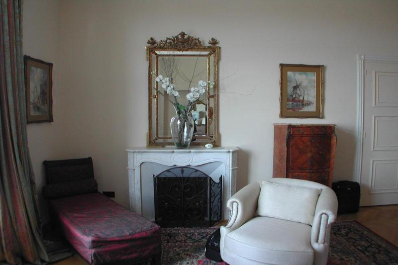 Red recliner sofa and a white sofa placed over a rug in front of a fireplace in Cannes villa