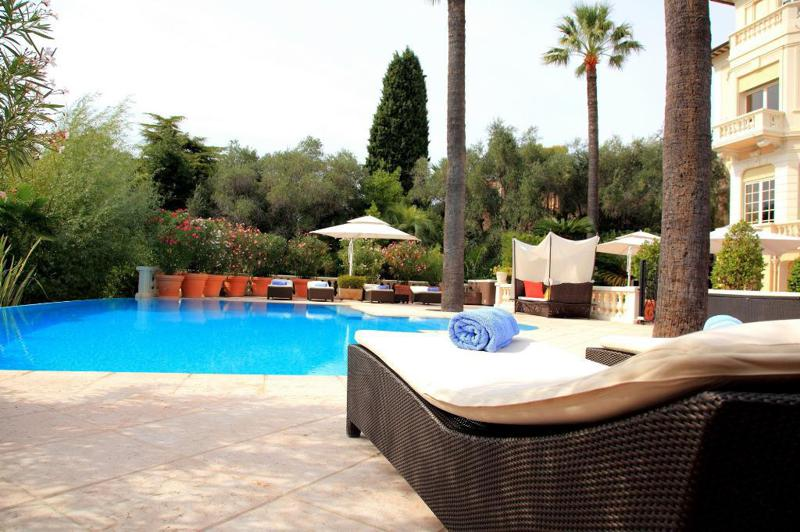 Swimming pool surrounded by lounge chairs and palm trees in a Cannes party villa