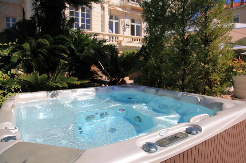 Outdoor jacuzzi with water in it in the garden of a Cannes rental villa