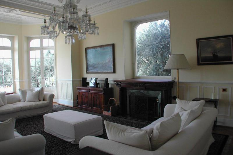 White couches and fireplace in the living room with chandelier and paintings on the wall in a Cannes villa