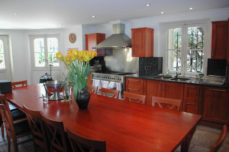 Kitchen with wooden cabinets and a dining table with a flower pot on top in Cannes