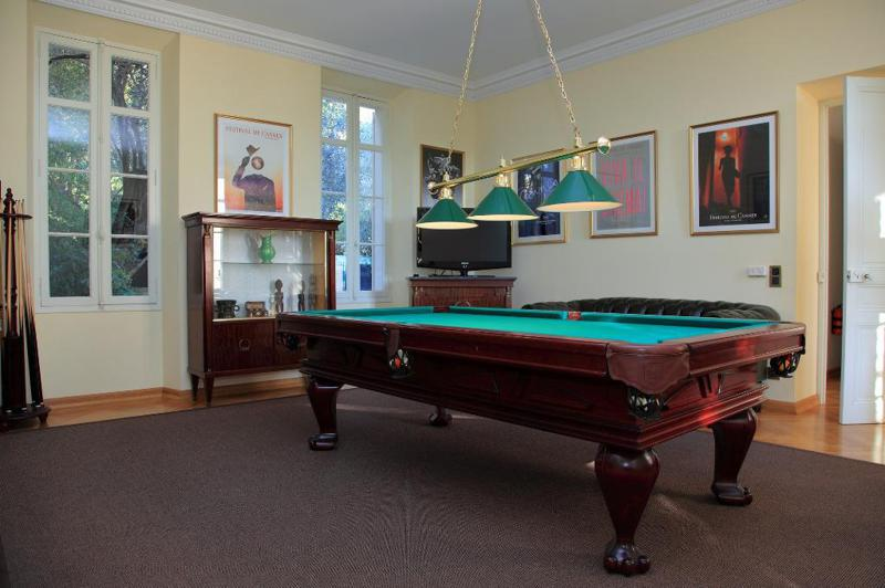 Pool table in a room with couches and framed posters in a Cannes rental villa