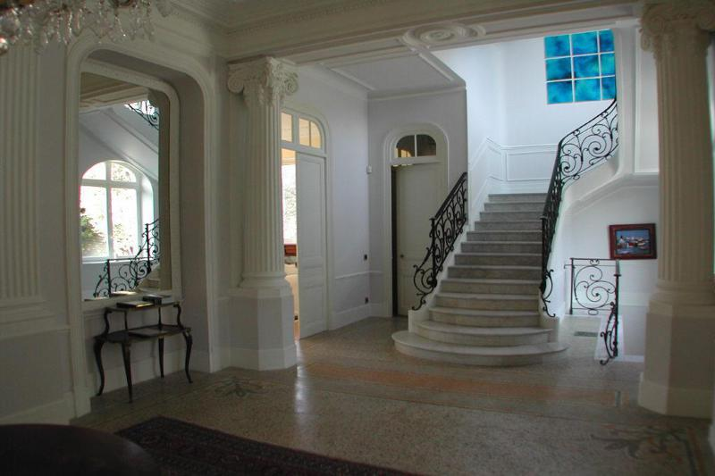 Indoor white stone stairs with pillars on both sides and door opening to the living room in the hallway