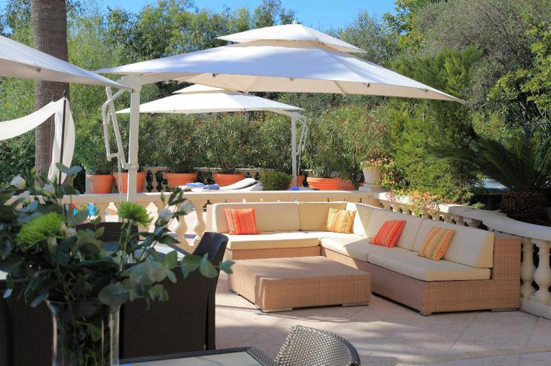 Outdoor relaxing area with couches and umbrellas for shades surrounded by plants and trees in a Cannes corporate party villa