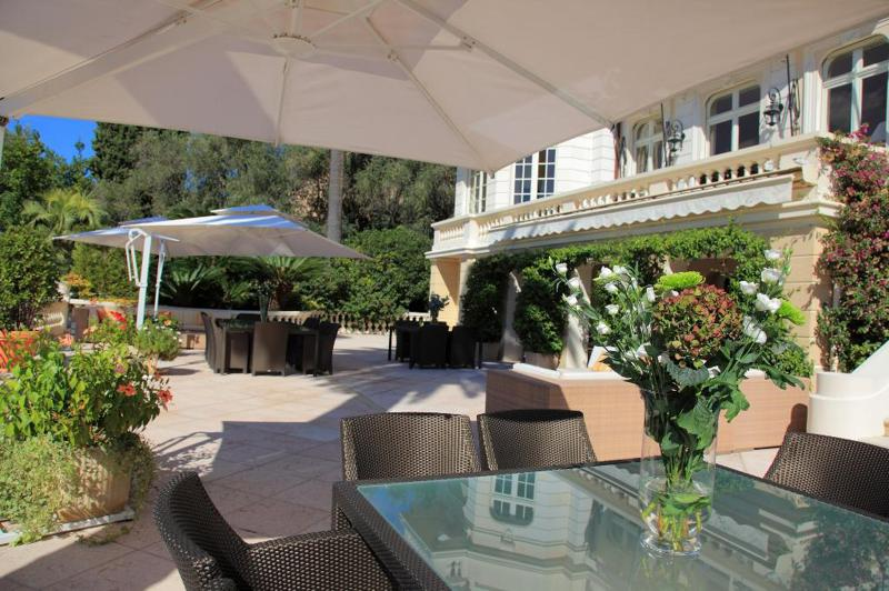 Tables, chairs and lounge chairs in the garden overlooking Cannes group Villa