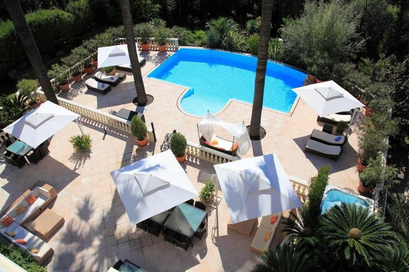 Top view of a swimming pool and garden with couches, chairs and tables in a Cannes Lions event villa