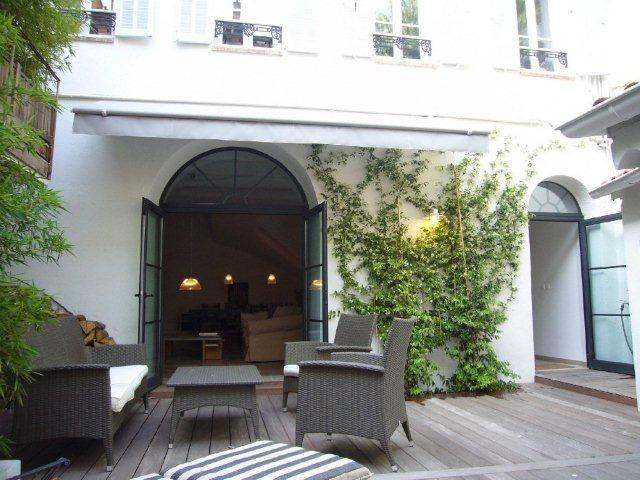 Outdoor deck with furniture and overlooking the living room of a Cannes rental event townhouse