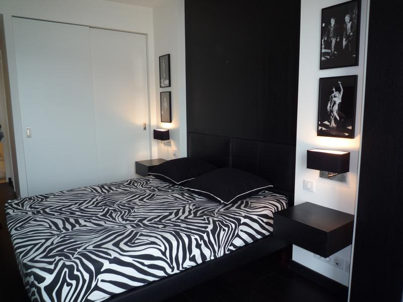 Double bedroom with black headboard and pillows and a wall fitted wardrobe