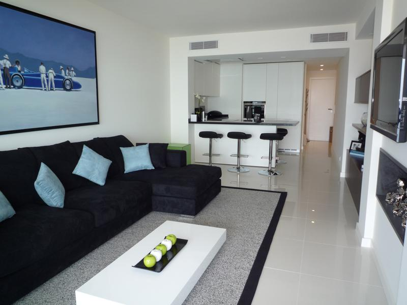 A painting on the wall behind a black couch in the living room of a Cannes event apartment with open kitchen