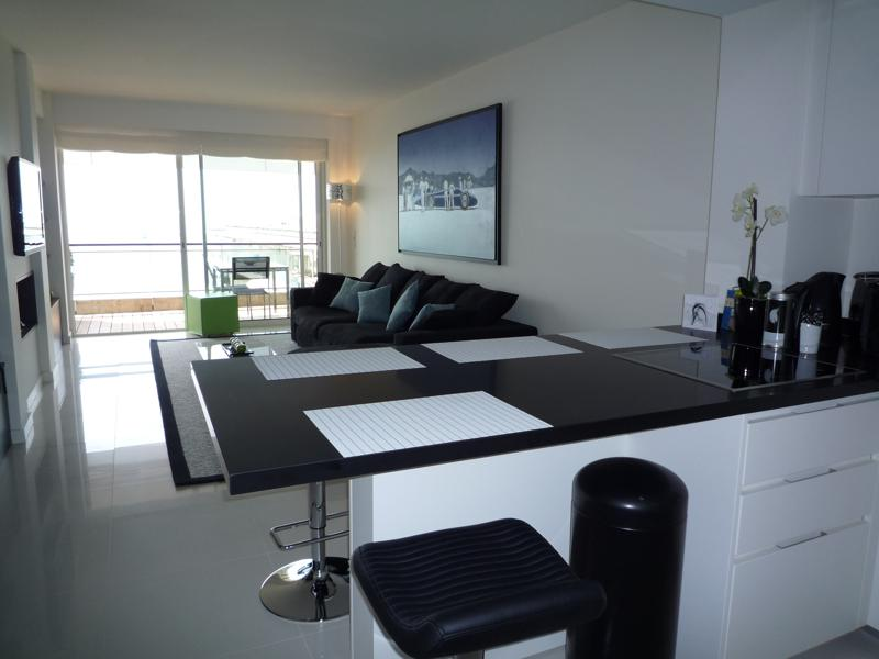 View of living room and terrace of a Cannes rental apartment from the open kitchen with black countertop and bar stools