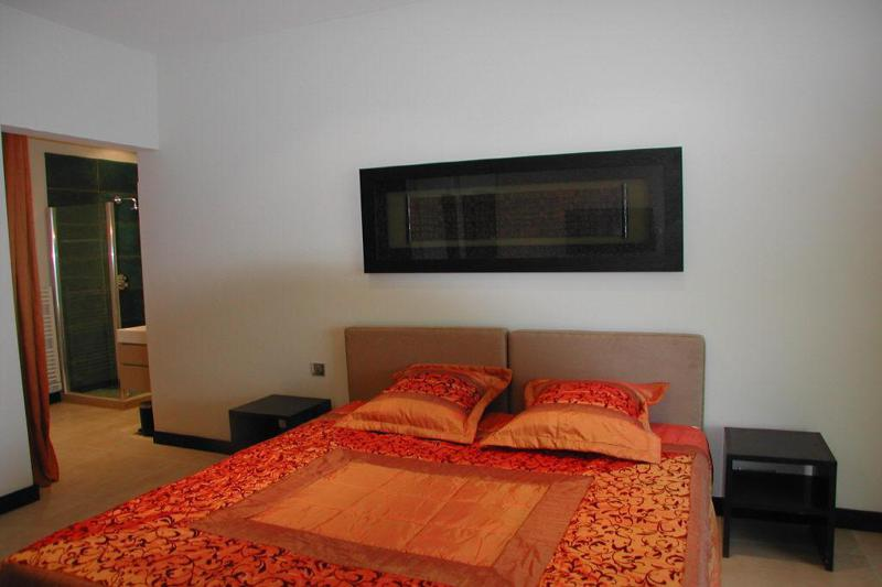 Double bed with matching orange printed sheet and pillow and attached bathroom