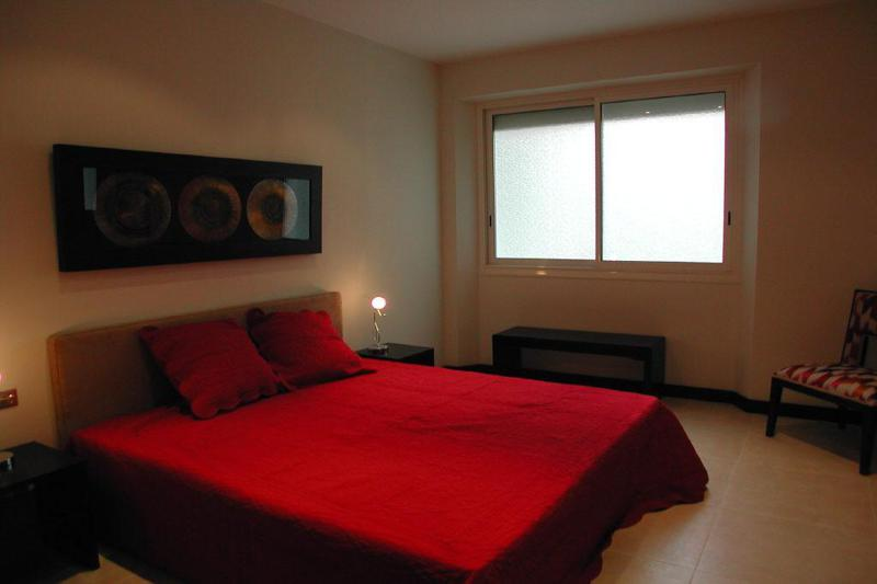 Double bed with red blanket, a painting on the wall behind and a chair in the corner