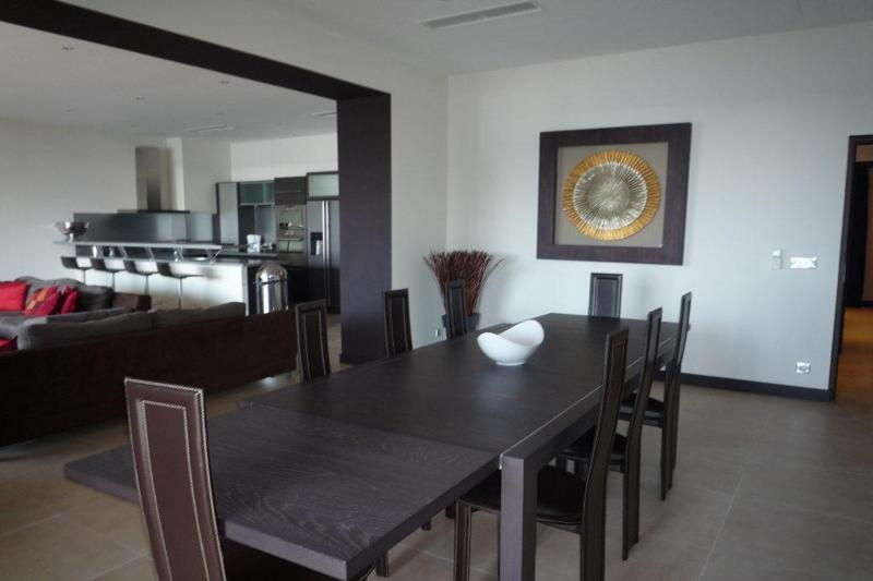 Dining area with a brown table and chairs next to the living room and open kitchen of a Cannes rental apartment