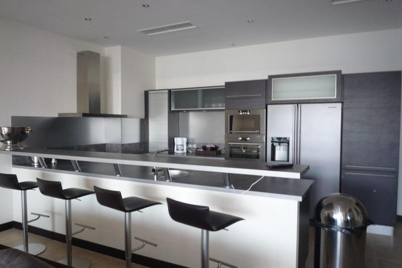 Kitchen with stainless steel appliances and bar stools on another side of countertop in Cannes