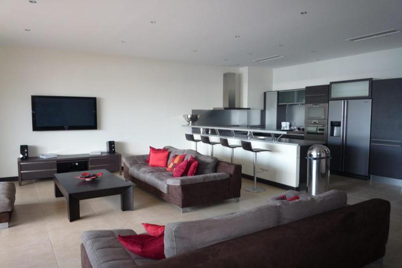 Brown couch set in a living room with open kitchen, a tv, bar stools and a centre table in Cannes group accommodation