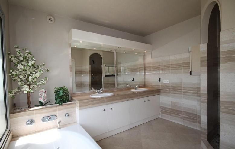 Bathroom with shower plants next to a bathtub and a dual sink with mirror over it and white cabinets underneath it in Cannes