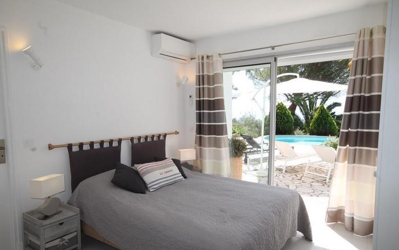 Grey bedsheets and an air conditioner in a double bedroom opening up to a swimming pool in Cannes rental villa