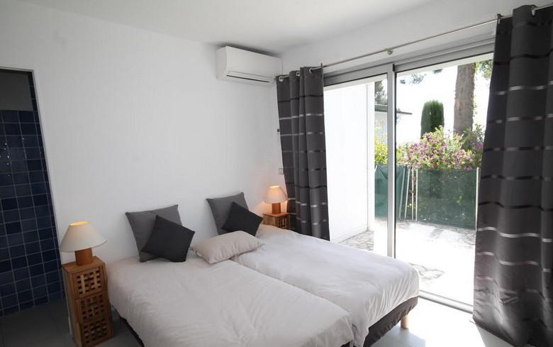 2 single bed with white sheets and black pillows joined together in a Cannes villa bedroom with natural light.