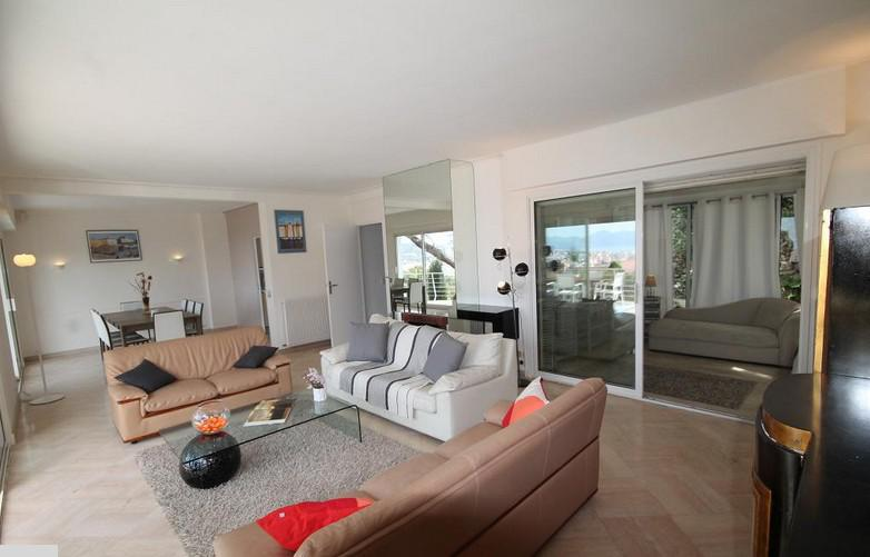 Living room with 3 couch sets and an open dining area with a dining table in a Cannes villa