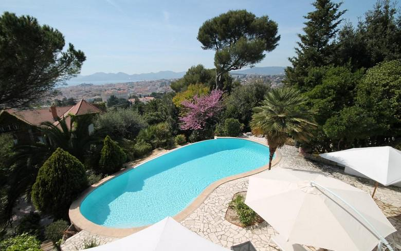 Swimming pool with city and sea views surrounded by a garden in a Cannes private rental villa for Lions