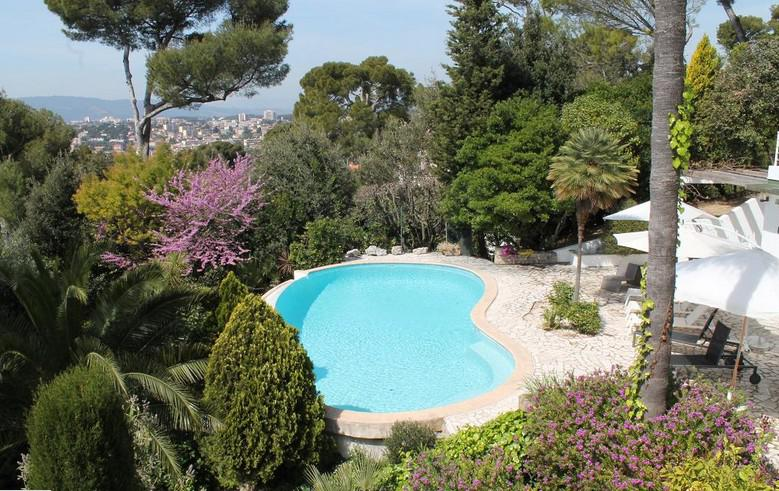 Top view of a kidney-shaped pool in a Cannes corporate rental villa with lounge chairs and canopies, surrounded by trees.