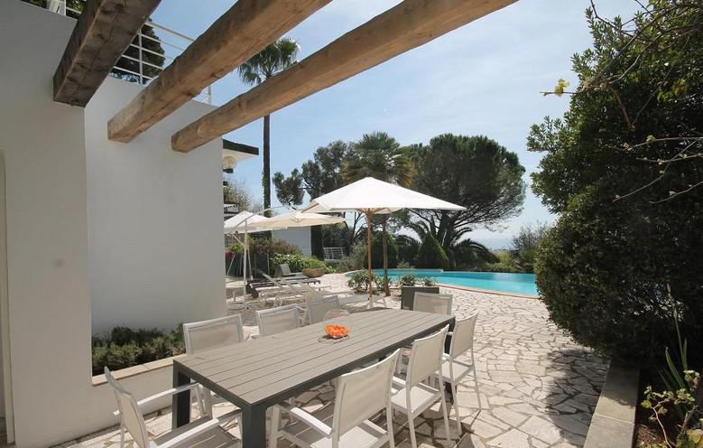 Outdoor dining table and sunbathing lounge with relaxing area next to the swimming pool in a Cannes rental villa for groups