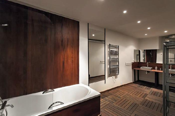 Bathroom with wooden interiors and a bathtub in a Cannes group accommodation