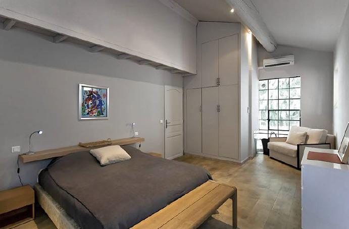 Double bedroom with white closet and sofa in a loft styled apartment for group rental in Cannes