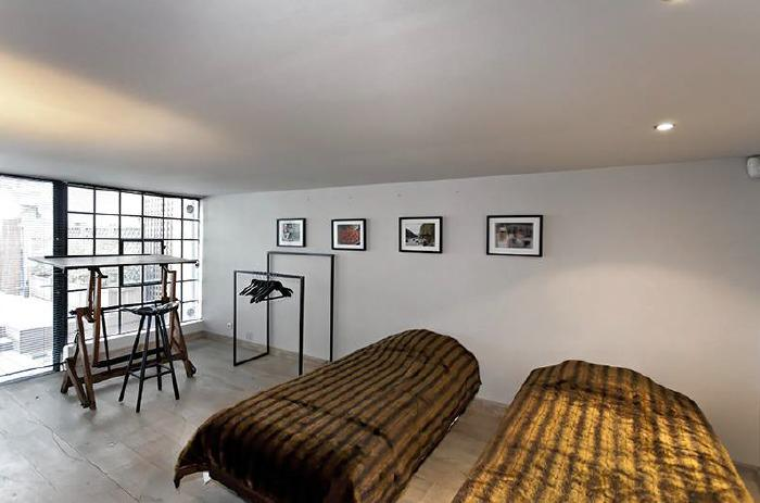 2 single beds with wall paintings and a window wall in Cannes