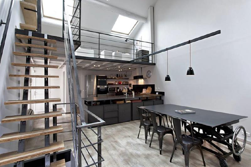 Black theme open kitchen with dining table and stairs in a Cannes group accommodation