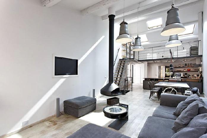 Hanging fireplace in a living room with grey couches and cushions and loft style interiors in a Cannes rental Villa