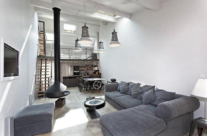 Loft style apartment living room with open kitchen, hanging lights and fireplace in a Cannes rental Villa