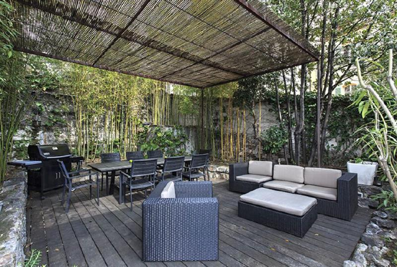 Outdoor patio with black couch set and table, surrounded by green plants in a Cannes group rental accommodation
