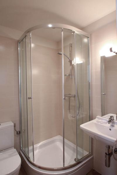 Glass enclosed standing shower in a bathroom with sink and toilet