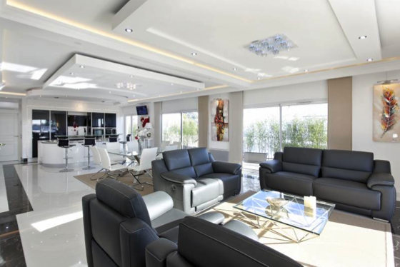 Black leather couch sets with dining table and open kitchen in the living room of a Cannes rental event apartment