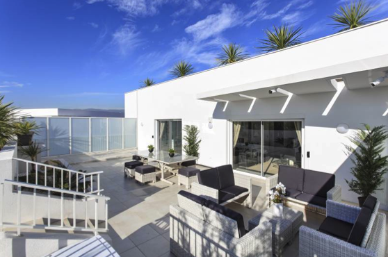 Terrace with couches and chairs on the top floor of a building in Cannes corporate accommodation with views