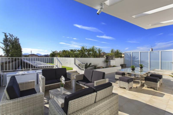 Couches and stools with tables on the terrace with views in a Cannes group accommodation