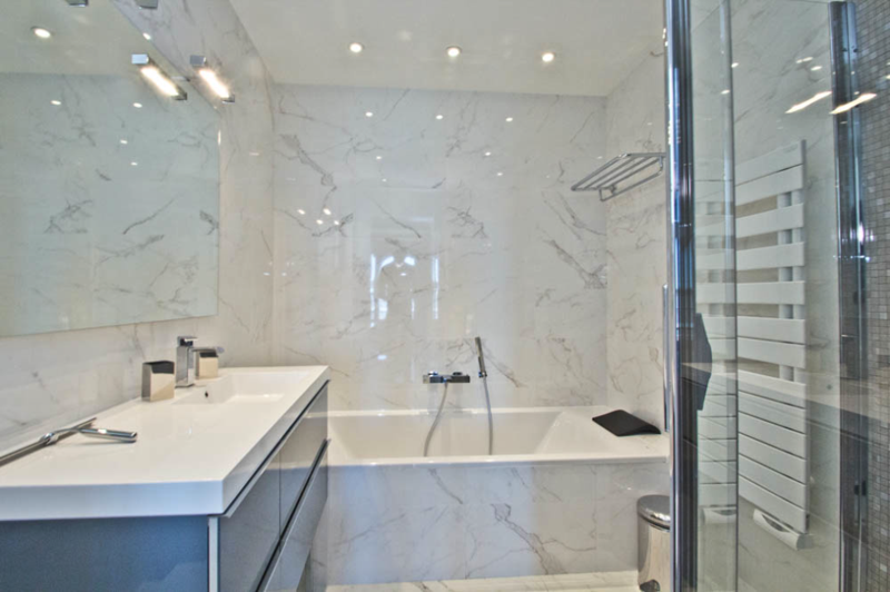 Bathroom with white marble tiles and bathtub in Cannes apartment