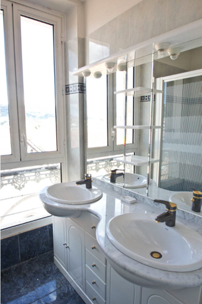 White vessel sinks and a large mirror in the bathroom