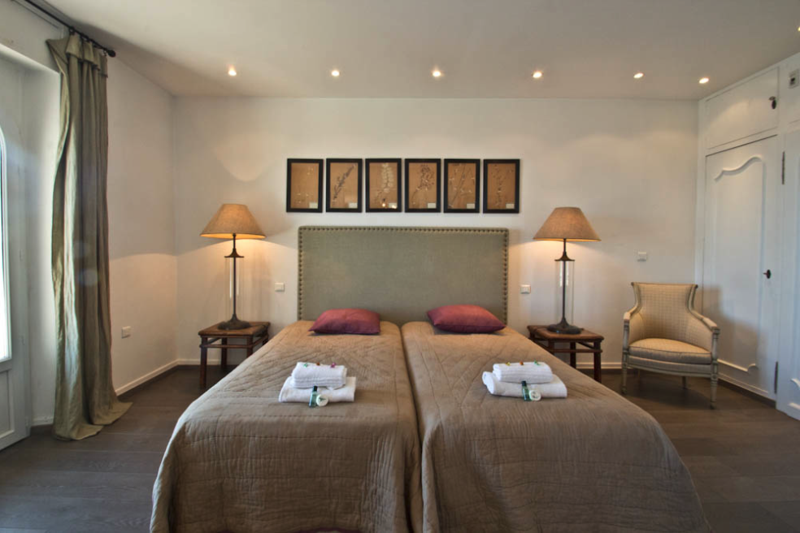 2 single beds with lampstands and pink cushions in a wooden floored bedroom in Cannes centre.