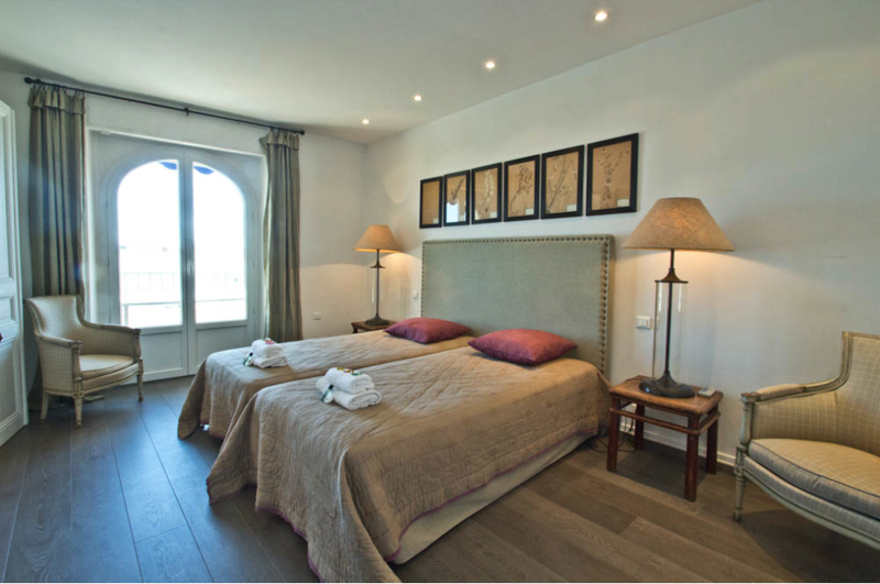 Bedroom with cream, light brown and beige coloured decoration and a door to balcony for group in Cannes