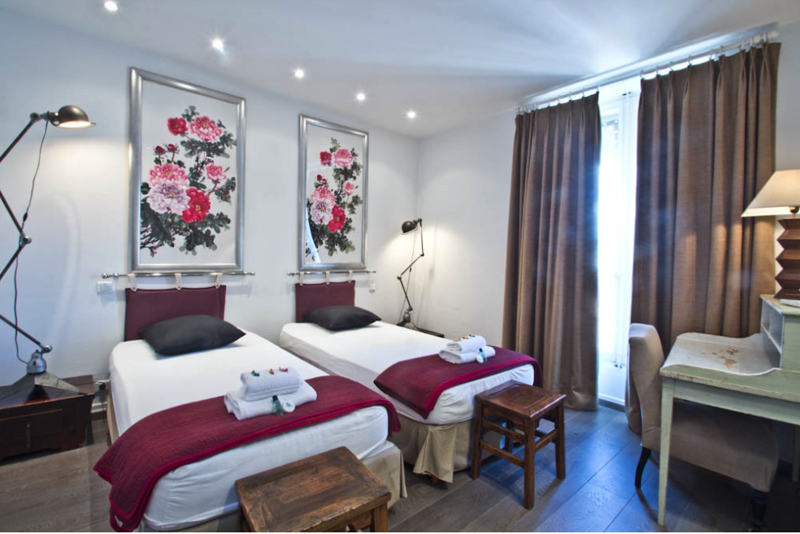 2 single beds with white sheets and maroon blankets in a bright room next to Cannes convention centre