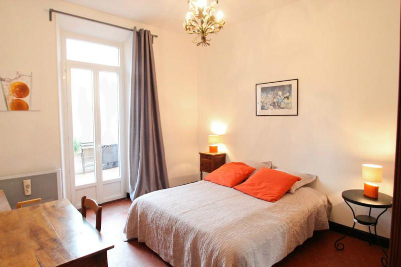 Double bedroom with a cream blanket and orange pillows with wooden table and chair and door to terrace in Cannes