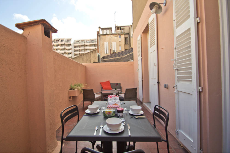 Dining table, couch and chairs in the backyard terrace of a Cannes apartment