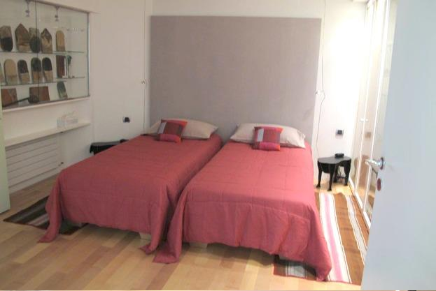 2 single beds with red coloured sheets and white pillows in a bedroom with wooden floor in Cannes