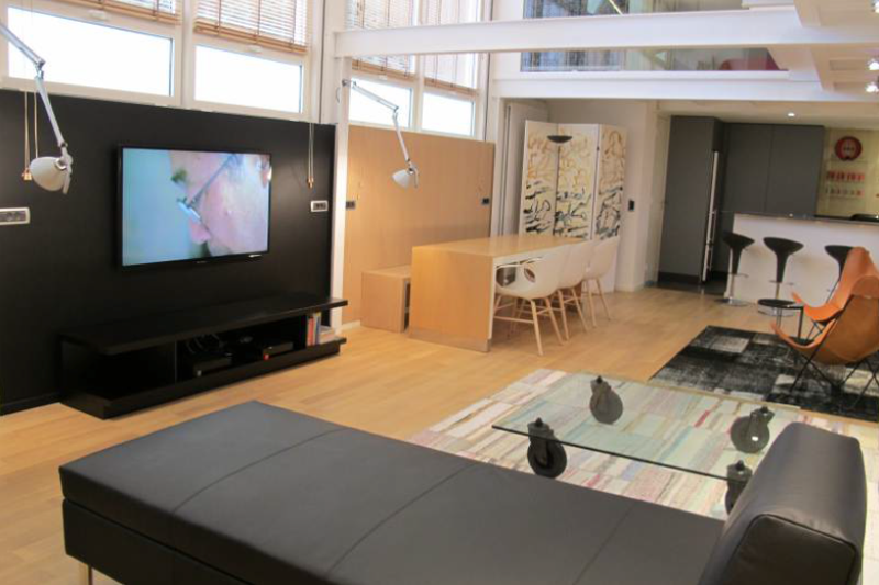 Duplex loft with a black recliner sofa, a dining table and an open kitchen with stools in a Cannes corporate apartment.