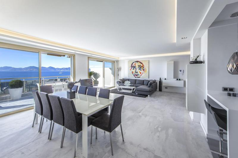 Sea views from a living room with a conference table for meetings and opens up to a balcony in a Cannes lions penthouse